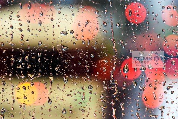 Abstract bokeh lights seen through raindrops streaking down a windscreen