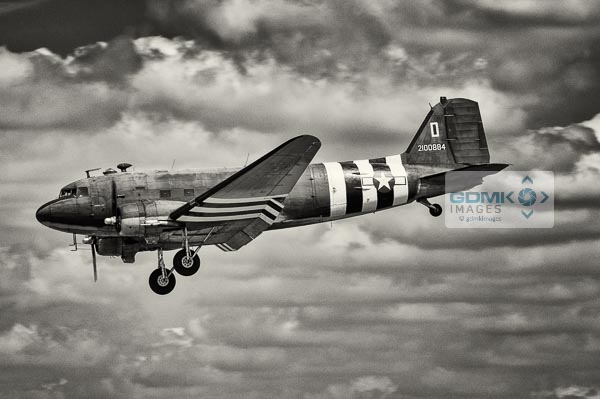 Black and white C47 Dakota wearing D Day invasion stripes. Side view of aeroplane as it lands