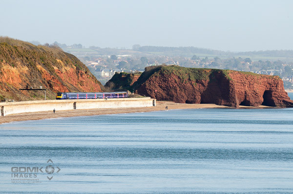 Looking across the sea towards the Dawlish coastline with a First Great Western train on the sea wall