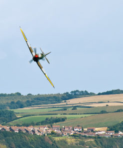 Spitfire turning hard as it passes over the English countryside