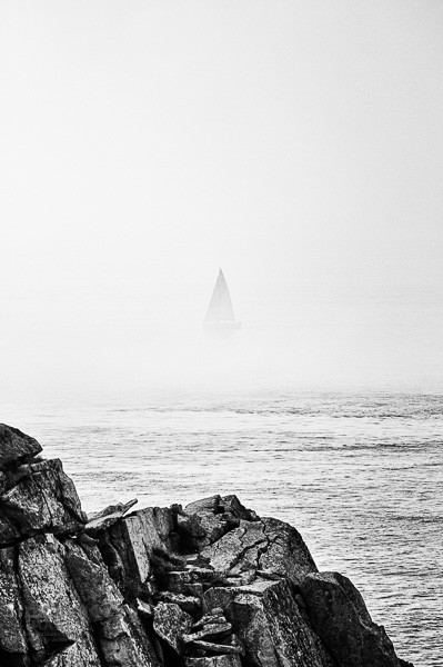 Sailboat disappearing into the sea mist at Pointe du Ra in Brittany