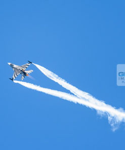 Belgian Air Force F-16 aeroplane trailing white vapour trails during an airshow display