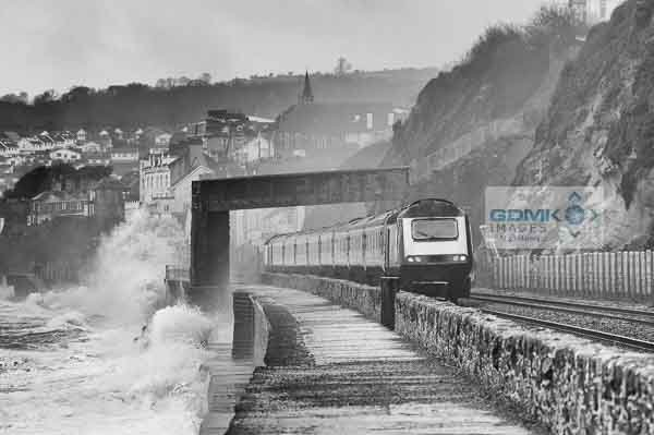 Winter storms pounding the seawall at Dawlish as a First Great Western passenger train passes