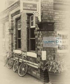 Antique effect photo of a 1960s scene showing 2 bicycles leaning against a station building.