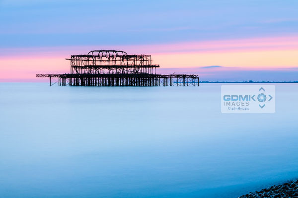 The derelict remains of Brighton West pier against the pastel colours of evening light