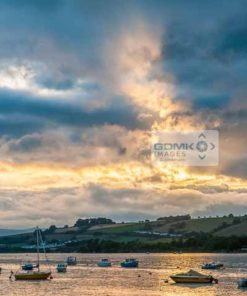Sun breaking through dramatic clouds over the River Teign near shaldon