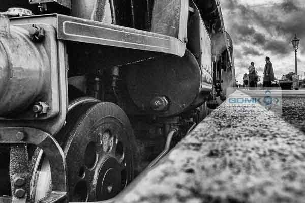 Platform level view of the front of a Bulleid Light Pacific steam loco standing in a platform in black and white