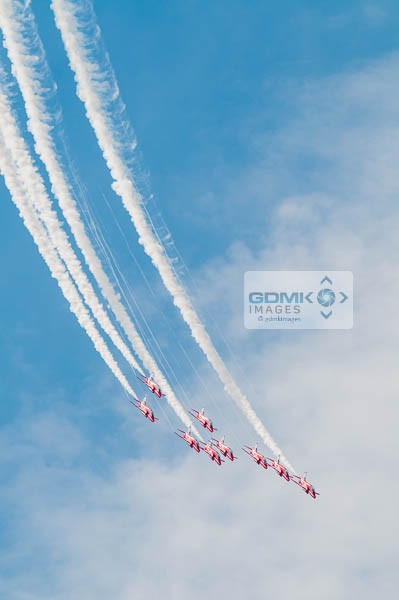 RAF Red Arrows flying in formation trailing white smoke