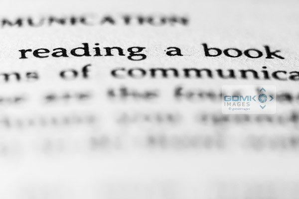 Closeup of text saying 'reading a book' in a paperback book