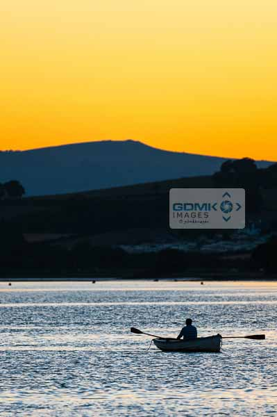Silhoutte of a man rowing on the River Teign as the sun sets over Dartmoor in the background