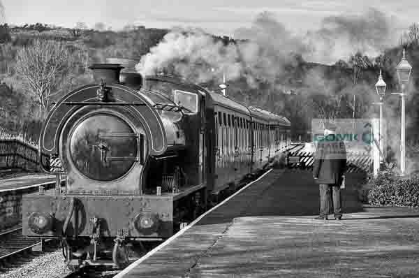 Black and white view of the station master waiting on the platform at Darley Dale railway station as a passenger train arrives