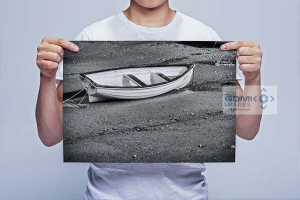 Man Holding Black and White Boat on a Beach Wall Art Print