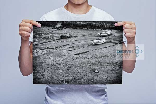 Man Holding Black and White Boats on a Beach Wall Art Prints