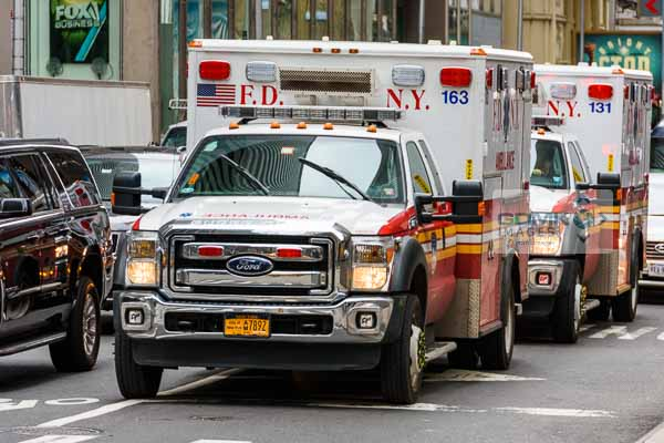 2 Fire Department of New York ambulances waiting in traffic on a New York road