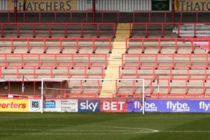 Looking across the pitch towards the goal and empty terraces of Exeter City Football ground at St James Park