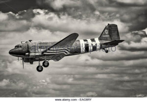 EAC6RY Black and white C47 Dakota wearing D Day invasion stripes. Side view of aeroplane as it lands
