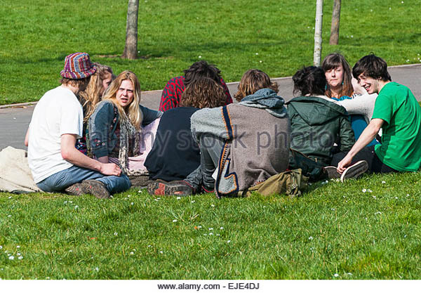 EJE4DJ Group of students sitting and relaxing on the grass in Northernhay Gardens Exeter